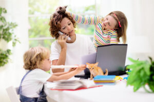 mother working from home with her children because their school is closed