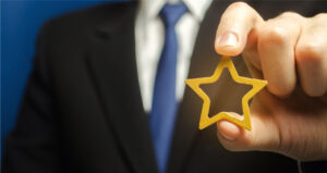 a man holds a gold star, a symbol of his success and excellence
