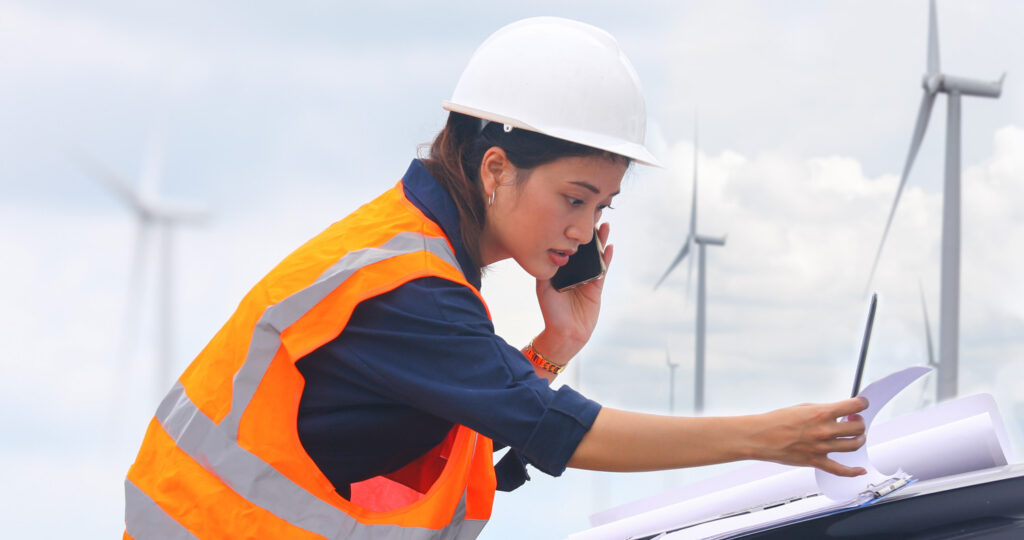 a young woman on a mobile phone and a laptop working on site at a wind turbine farm
