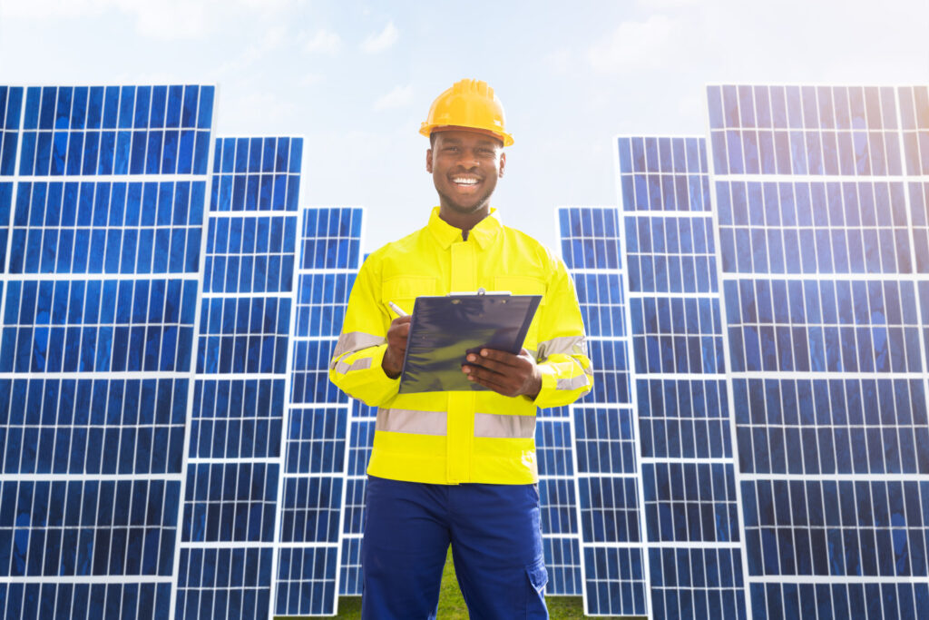 a man in a hard hat and hi-viz jacket standing in front of solar panels