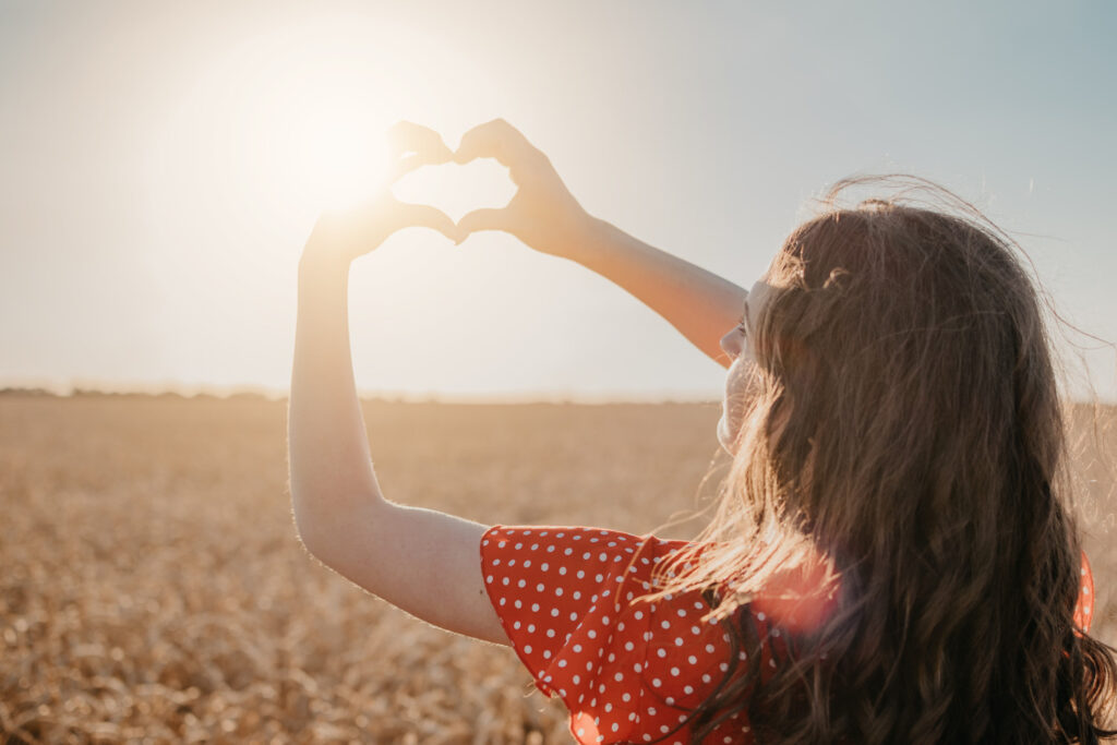 a young woman standing in a corn field making a heart shape with her hands around the sun